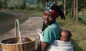 A 27-year-old Rwandan woman carries her 9-month-old baby on her back as she heads to the local market to sell avocados.