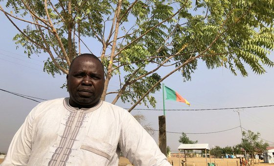 Luka Isaac, a Nigerian refugee representative in the Minawao camp in Cameroon, stands beneath a tree he planted as part of the planting of some 50,000 trees at a camp for Nigerian refugees in the far north-east corner of Cameroon.