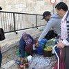 """2018年11月,一名巴勒斯坦妇女在""""大马士革门""""外卖橄榄,橄榄油和其他食品,这是耶路撒冷老城的大门之一。"""