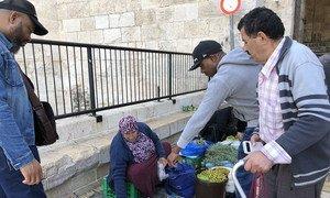 Une Palestinienne vendant des olives, de l'huile d'olive et d'autres produits alimentaires devant la porte de Damas, l'une des portes de la vieille ville de Jérusalem. Novembre 2018.