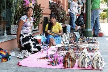 Dos jóvenes guaraníes venden artesanías en Asunción, Paraguay.