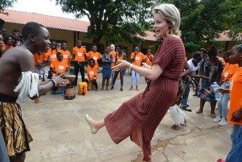 Rainha Mathilde da Bélgica interage com dançarino durante evento em Maputo, Moçambique.