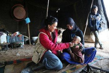 Una madre y su hijo junto  una trabajadora del PMA en el campamento de Rukban en Siria