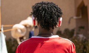 Mebratu, un joven de Eritrea de 16 años, escucha con audífonos su música favorita.