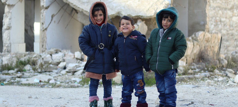 أطفال سوريون يرتدون ملابس وزعت عليهم من خلال برنامج تدعمه اليونيسف. 22 كانون الثاني/يناير 2019.