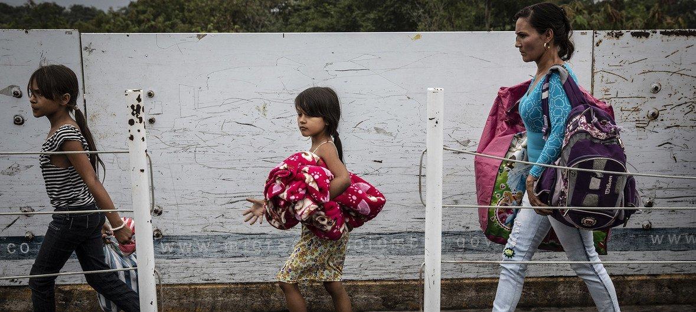 Refugiados e migrantes venezuelanos atravessam a Ponte Simon Bolívar, um dos sete pontos de entrada legais na fronteira Colômbia-Venezuela.
