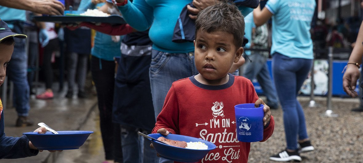 Venezuelan refugees and migrants near the Colombia-Venezuela border crossing queue for a meal at the Communal Kitchen Casa de Paso La Divina Providencia, supported by the UN refugee agency (UNHCR), where approximately 5,000 free meals are served to vulnerable Venezuelans on a daily basis
