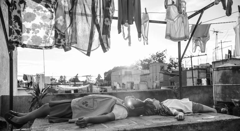 Yalitza Aparicio juega con un niño de la familia para la que trabaja en un escena de la película Roma.