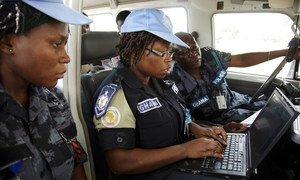 Akisaidiwa na wenzake wawili, Angela Ama Agyeman Sesime (katikati) wa Ghana, Polisi mshauri wa UNAMID akiandika ripoti baada ya doria katika kambi ya Zam Zam ya kuwahifadhi wakimbizi wa ndani eneo la Darfur Kaskazini, Sudan, Oktoba 2010.