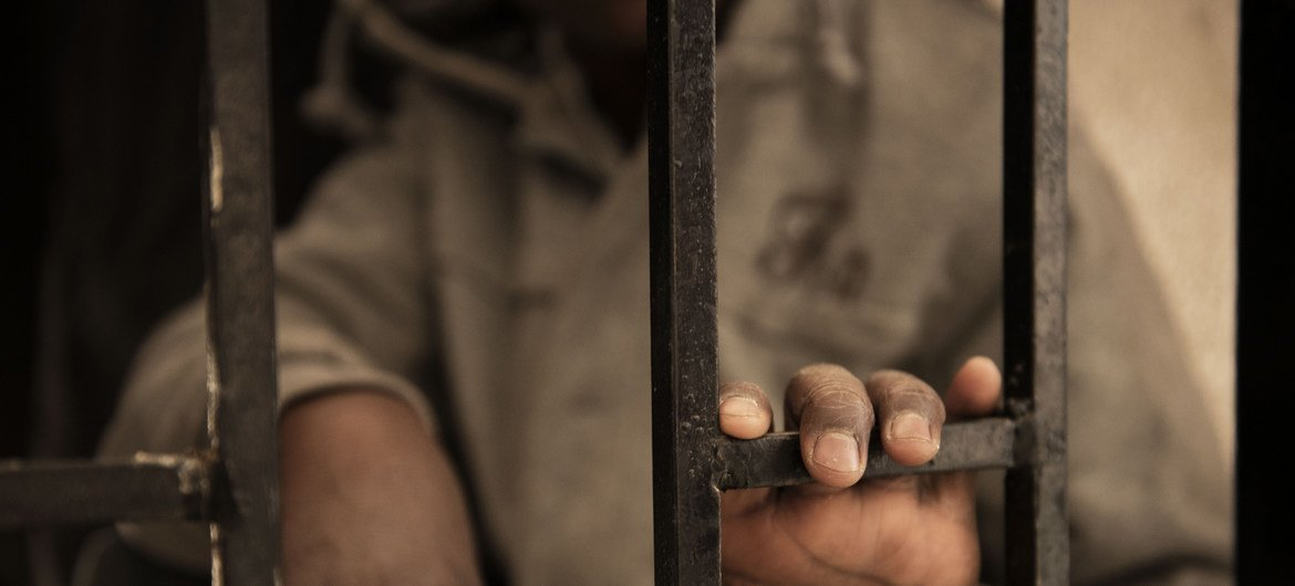 A migrant from Niger rests his hand on a gate inside a detention centre, in Libya, in 2017. He was arrested and detained before he was able to board a boat that was crossing to Italy.