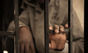 Fourteen-year-old Issaa, a migrant from Niger, rests his hand on a gate inside a detention centre, in Libya, in January 2017. His mother died two years ago in Niger. He managed to set aside US$450, which he hoped would pay for a crossing by boat to Italy. He was arrested and detained before he was able to board a boat.