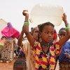 Une jeune fille portant un bidon d'eau dans le camp pour personnes déplacées de Barsalogho, au Burkina Faso en mars 2019. Au Burkina Faso, une fille sur deux (52%) est mariée avant l'âge de 18 ans et une sur 10 (10%) avant l'âge de 15 ans.
