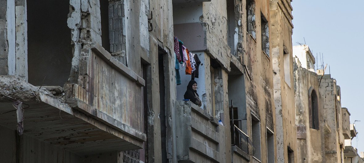 A woman stands on her balcony in the El Khalideh neighbourhood of the Old City of Homs, in Syria. (March 2019)