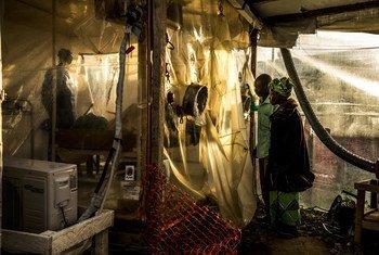 काँगो गणराज्य के बेनी इलाक़े में बना एक चिकित्सा केन्द्र, ईबोला संक्रमण के सन्देह में अपनी 15 वर्षीय बेटी की जाँच-पड़ताल देखते हुए माता-पाता. (जनवरी 2019)