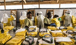 Health workers put their Personal Protective Equipment on before entering the zone where people suspected of having Ebola are held in quarantine to be monitored and treated at the Ebola Transition Centre (January 2019)