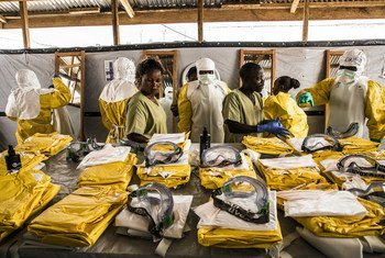 Des agents de santé revêtent leur équipement de protection individuelle avant d'entrer dans la zone où les personnes potentiellement atteintes du virus Ebola sont placées en quarantaine pour être suivies et traitées (janvier 2019).