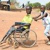 Massouron Camara, de 18 anos, da Côte d'Ivoire, empurrado na sua cadeira de rodas pelo irmão, Abib