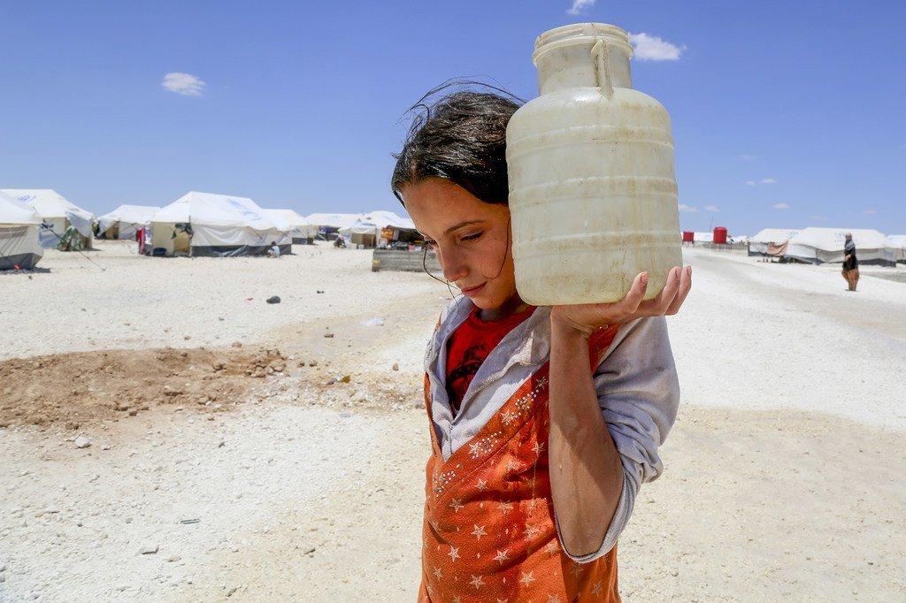 在叙利亚拉卡城以北50公里处的一个临时营地中,12岁的女孩Horriya抬着一个水罐子。(2017年图片)