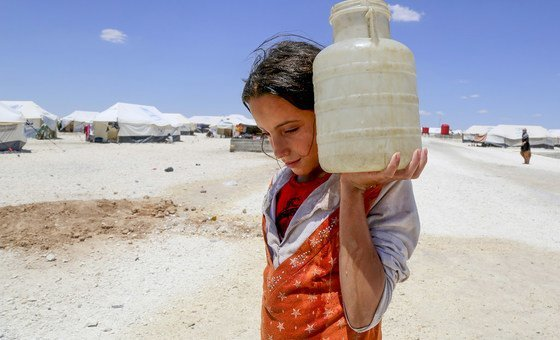 In the makeshift camp at Ain Issa, 50 km north of the Raqqa in the Syrian Arab Republic, Horriya, 12, carries a jerrycan of water (2017).