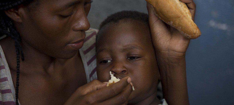 Mãe alimenta filho de dois anos na Escola Samora Machel, que está servindo de abrigo