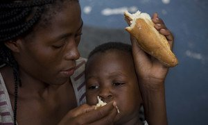 A mother feeds her 2-year-old son at the Samora Machel school where they were brought after their homes were destroyed and flooded in Buzi, Mozambique.