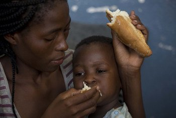 मोज़ाम्बिक के बुज़ी में एक अस्थायी राहत शिविर में अपने दो साल के बच्चे को खाना खिलाती एक मां.