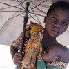 Aruminda segura o irnão, António, em um campo para deslocados em Dondo, Moçambique