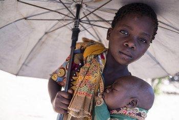 Aruminda sostiene a su hermano, Antonio, en un campo para desplazados en Dondo, Mozambique. El ciclón Idai desplazó a miles de personas