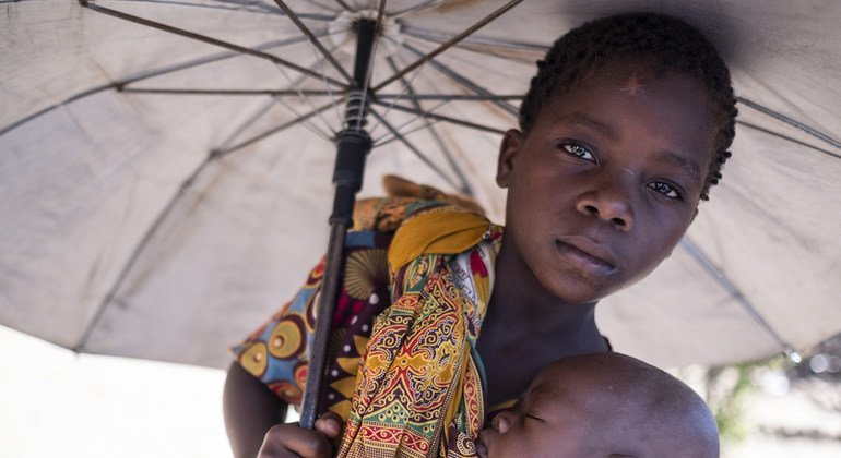 Aruminda holds her brother, Antonio, at a camp set up for displaced people at the Jehovas Witness Centre in Dondo, Mozambique. Cyclone Idai displaced thousands of people.