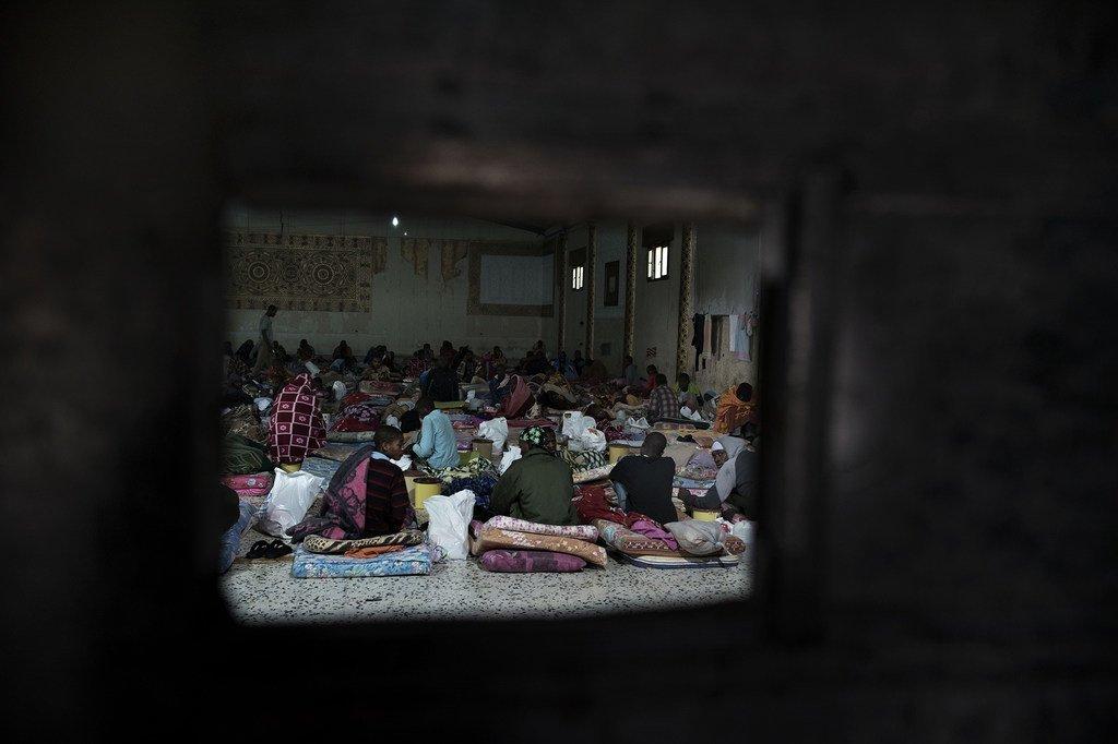 Derrière cette porte en fer, des migrants sont assis sur des matelas posés à même le sol dans un centre de détention en Libye.