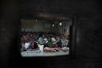 从一扇铁门的开口看进去,利比亚一个拘留中心的移民坐在地板上的床垫上。