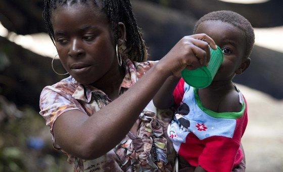 Mãe dá de beber ao filho na Escola Samora Machel, em Búzi, que acolhe deslocados do ciclone Idai