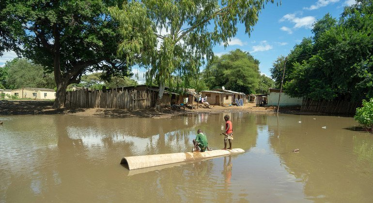Dos jóvenes juegan en una enorme piscina creada por las inundaciones del ciclón Idai en un campamento de refugidos en Zimbabwe.