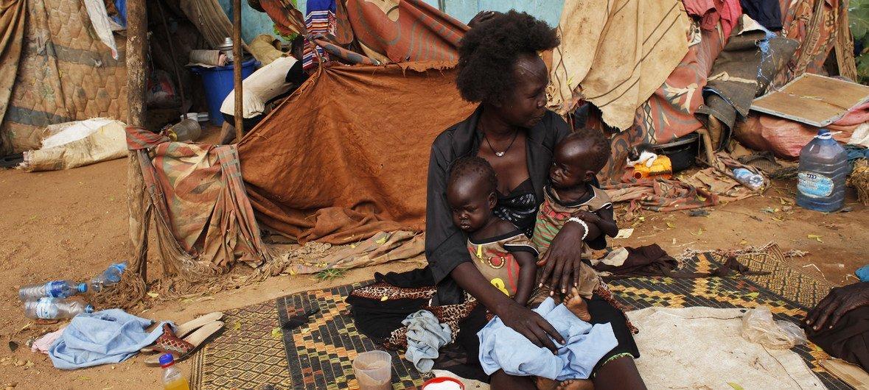 Deux jumelles, Elizabeth et Madelina, qui souffrent de malnutrition, sont dans les bras d'une membre de leur famille dans la rue où elles vivent à Juba, au Soudan du Sud.