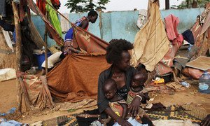 Twins Elizabeth and Madelina, who suffer from malnutrition, are being held by a relative in the street, where they live, in  Juba, South Sudan. (2018).