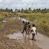 Crianças numa estrada de Búzi, em Moçambique, danificada pelo ciclone Idai