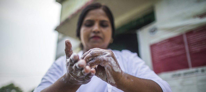 Enfermeira obstetra lava as mãos antes de fazer um exame em Shrawasti, na Índia