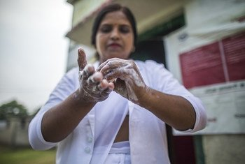 An Auxiliary Nurse Midwife washes her hands before she examines a pregnant woman as part of Village Health and Nutrition Day in Shrawasti, India.