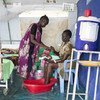 A newborn baby  is getting a bath by it's grandmother at the UNICEF supported maternity ward in the POC in Malakal, South Sudan. .