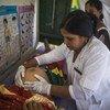 भारत के श्रावस्ती में गर्भवती महिला की जांच करती एक स्वास्थ्य कर्मचारी.