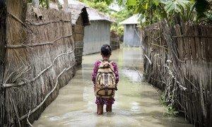 Una niña camina a su escuela en el agua tras graves inundacions ocurridas en Bangladesh en agosto de 2016.