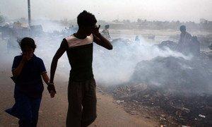 बांग्लादेश की राजधानी ढाका में जलते कूड़े के ढेर के पास से गुज़रते लोग.