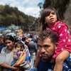 Laila Dalila León, de tres años, mira hacia la aduana colombiana en Rumichaca, en el frontera entre Colombia y Ecuador, sentada sobre los hombros de su padre.