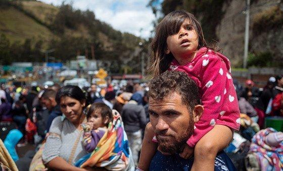 三歲的萊拉·達利拉·萊昂坐在父親的肩膀上,看著厄瓜多爾與哥倫比亞交界的魯米查卡的哥倫比亞海關(2018年8月9日)。