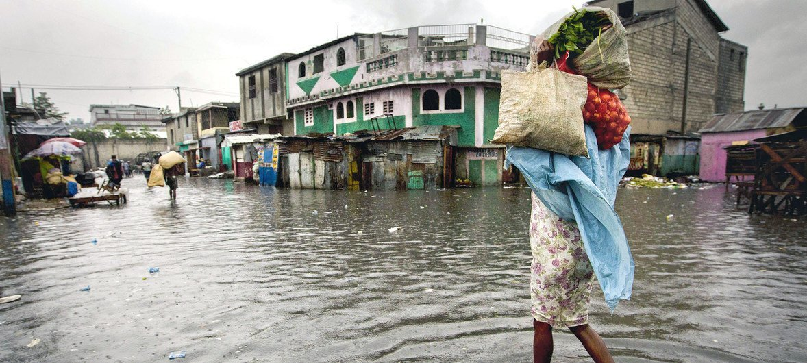 A woman walks through a flooded market in Port au Prince, Haiti, after Hurricane Sandy wreaked havoc on the Caribbean island in 2012.