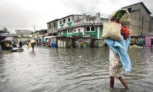 """一名妇女走过海地太子港的一个被水淹没的市场,飓风""""桑迪""""2012年对加勒比海岛屿国家造成了严重破坏。"""
