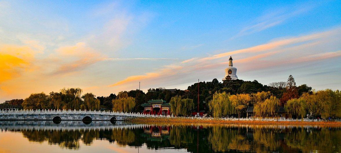黄昏时分的北京北海公园,琼华岛上的白塔倒映在湖心。