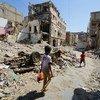 यमन के अदन में ध्वस्त हो चुके शहर के मुख्य इलाक़े से गुज़रते बच्चे.