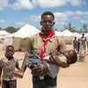 Lucio Carlos, a volunteer social mobiliser, carried Luisa Daniel, 5, suffering from fever and vomiting to a medical tent where she was tested for Malaria. Dondo, Mozambique.