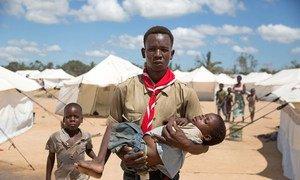O voluntário Lúcio Carlos carrega nos braços a pequena Luísa Daniel para uma tenda em área de assentamento no Dondo.